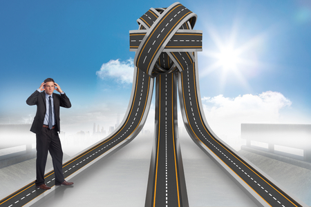 tangled roads: Stressed businessman with hands on head against tangled roads in a ball Stock Photo