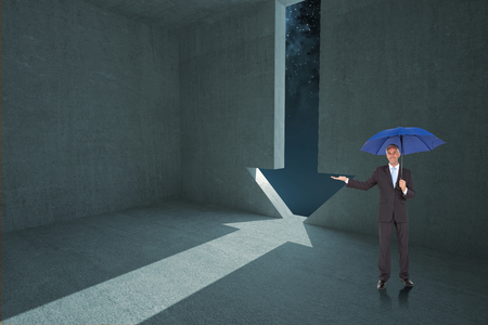 Peaceful businessman holding blue umbrella against arrow door in dark room photo