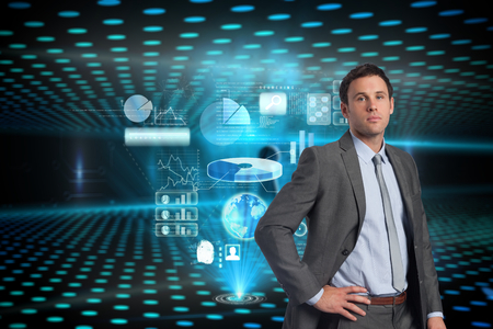 Serious businessman with hand on hip against keyhole on technological glowing background photo