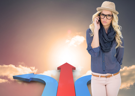 Serious trendy blonde on the phone against red and blue curved arrows pointing against sky photo