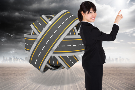 tangled roads: Smiling businesswoman pointing against tangled roads in a ball