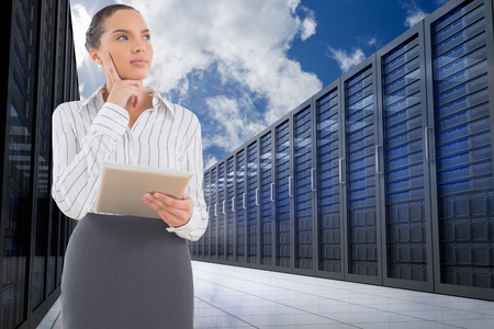 Confused businesswoman using a tablet pc against server hallway in the sky photo