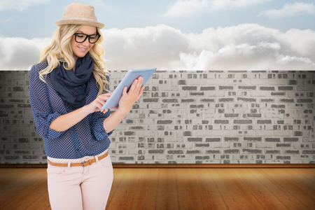 Smiling trendy blonde using tablet computer against balcony and bright sky photo