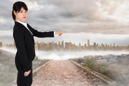 urban sprawl: Focused businesswoman pointing against stony path leading to large urban sprawl
