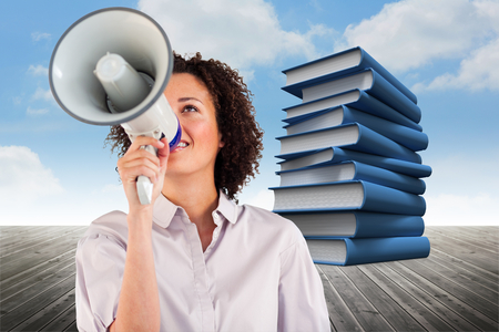 Businesswoman shouting through megaphone  against stack of books against sky photo