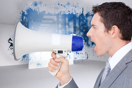 Businessman using a megaphone  against splash showing data hallway photo