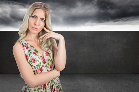 Frowning pretty blonde wearing flowered dress posing against balcony and stormy sky photo