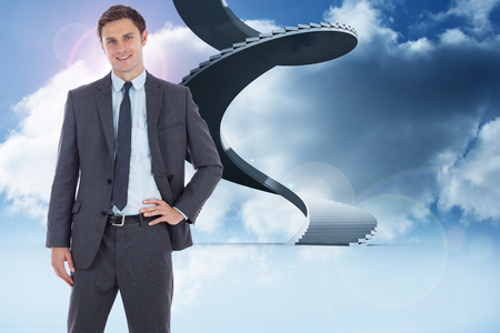 Smiling businessman with hand on hip against winding staircase in the sky photo