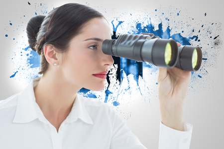 Business woman looking through binoculars against splash on wall revealing server tower photo