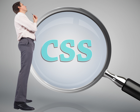 Thinking businessman holding pen against magnifying glass showing css word Stock Photo - 26849056