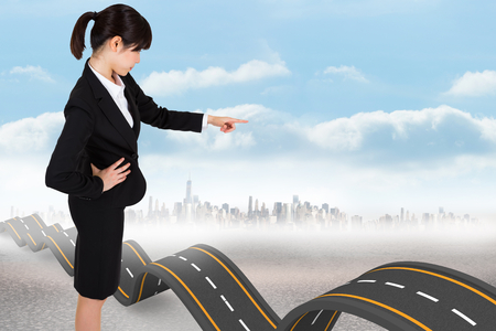 bumpy road: Focused businesswoman pointing against bumpy road backdrop