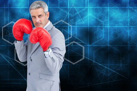 Tough businessman with boxing gloves against abstract technology background photo