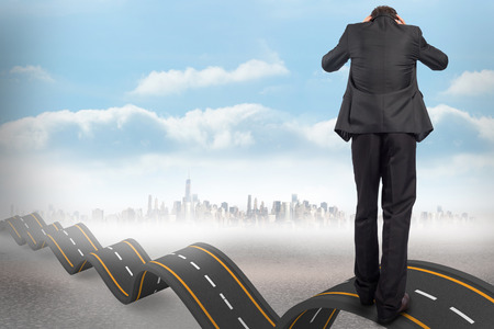 bumpy: Stressed businessman with hands on head against bumpy road backdrop Stock Photo