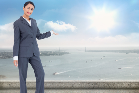 Standing businesswoman presenting against balcony overlooking city photo