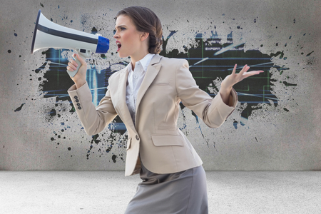 Furious stylish brown haired businesswoman shouting in a megaphone against splash on wall revealing technology interface photo