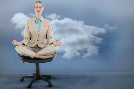 Peaceful chic businesswoman sitting in lotus position on swivel chair against clouds in a room photo