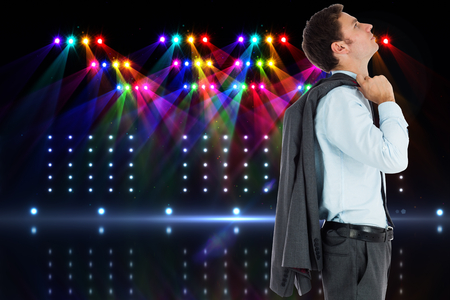 Serious businessman holding his jacket against cool nightlife lights photo
