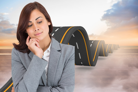 bumpy road: Smiling thoughtful businesswoman against bumpy road backdrop Stock Photo
