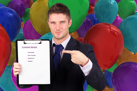 Businessman with customer service report against colourful balloons photo