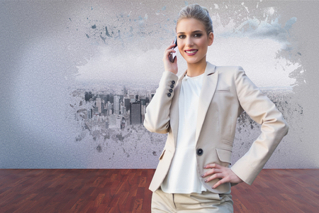 Cheerful elegant businesswoman on the phone against splash on wall revealing cityscape photo