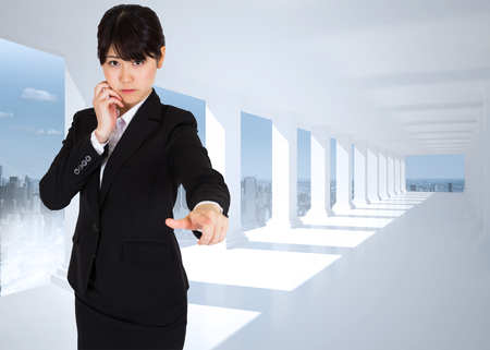 Thoughtful businesswoman pointing against bright white hall with columns photo