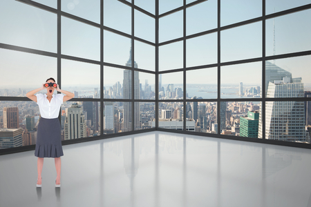 Shocked elegant businesswoman looking through binoculars against room with large window showing city photo