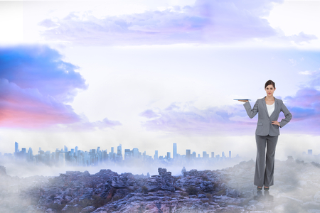 Smiling businesswoman holding tablet pc against misty landscape photo