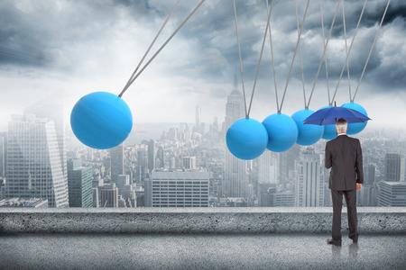 newton's cradle: Businessman holding umbrella against newtons cradle above city Stock Photo