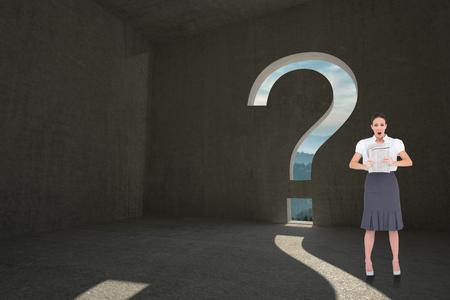 Shocked stylish businesswoman holding newspaper against question mark door in dark room photo