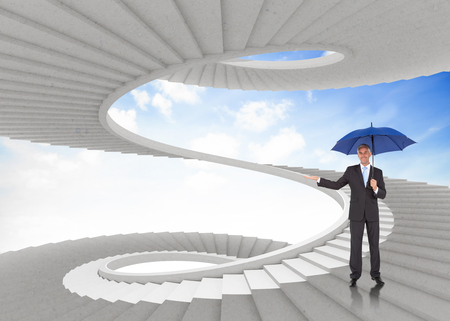 Peaceful businessman holding blue umbrella against spiral staircase in the sky photo