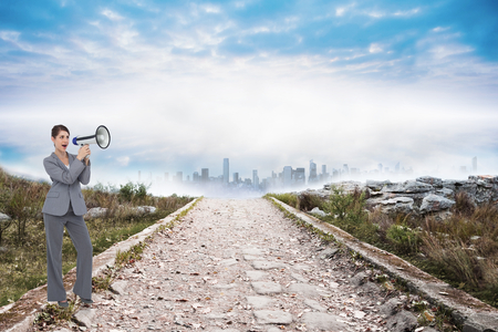 Businesswoman with loudspeaker against stony path leading to misty cityscape photo