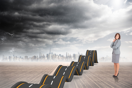 bumpy: Smiling thoughtful businesswoman against bumpy road backdrop Stock Photo
