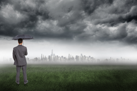Rear view of classy businessman holding grey umbrella against city on the horizon photo