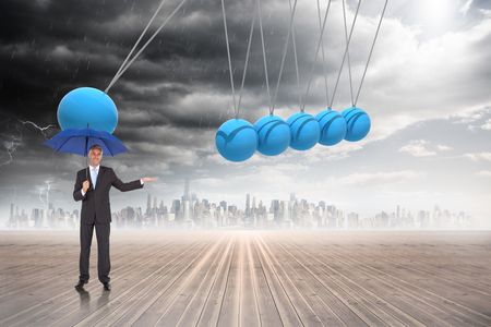 Peaceful businessman holding blue umbrella against newtons cradle above city photo