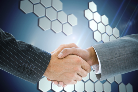 Composite image of business handshake against technological\ background with hexagons