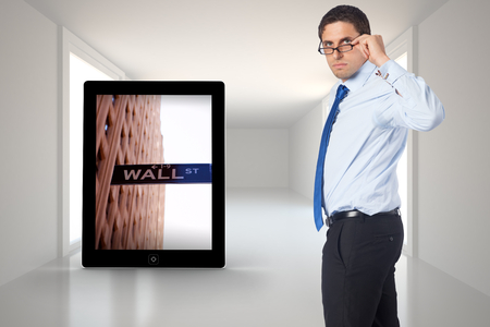 Thinking businessman tilting glasses against digitally generated room photo