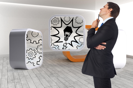 Thinking businessman holding pen against orange structure in a grey room photo