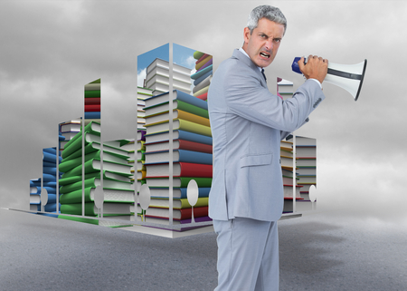 Furious businessman posing with loudspeaker against cloudy dull sky photo