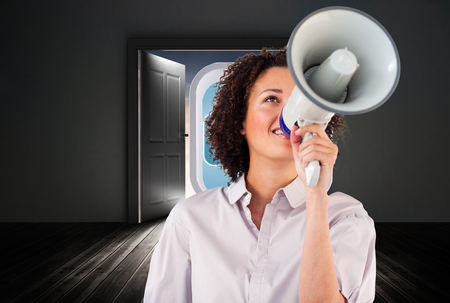 Businesswoman shouting through megaphone  against open doors in dark room photo