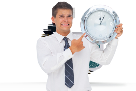 Anxious businessman holding and showing a clock against steps made out of books with open door photo