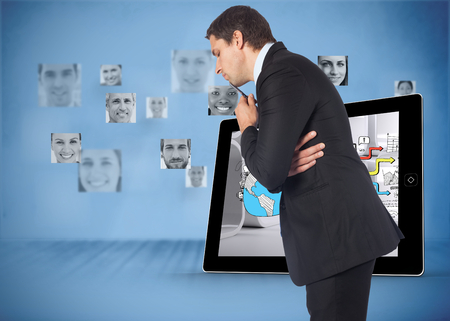 Thinking businessman holding pen against pictures of faces in blue room Stock Photo