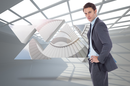 Serious businessman with hands on hips against white room with windows at ceiling photo