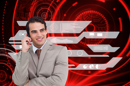Smiling salesman on his cellphone against shiny red circles on black background photo