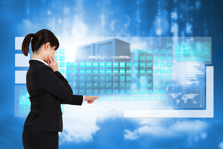 Businesswoman pointing against cityscape on cloud photo