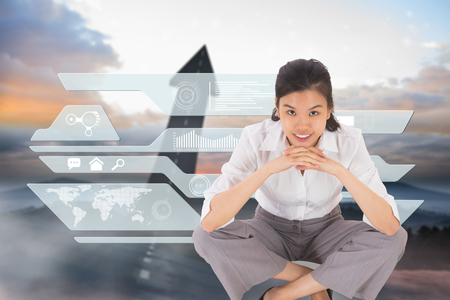 Smiling businesswoman sitting cross legged against road turning into arrow photo