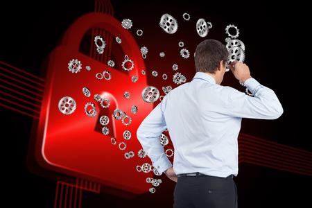 tilting: Thinking businessman tilting glasses against shiny red lock on black background Stock Photo