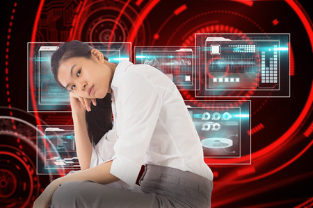 slumped: Businesswoman sitting cross legged leaning on hand against shiny red circles on black background Stock Photo