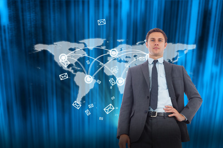 Stern businessman with hand on hip against futuristic blue black background photo