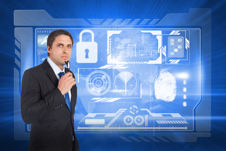 global thinking: Thinking businessman holding glasses against global technology background
