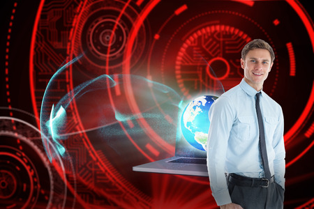Smiling businessman standing with hand in pocket against shiny red circles on black background photo